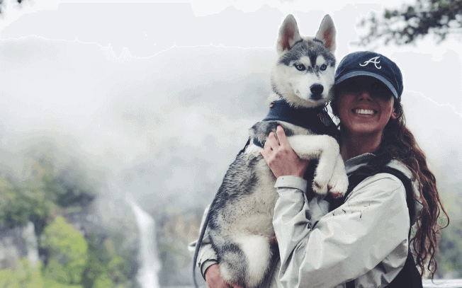 Girl holding a husky puppy outdoors