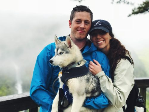 Man and woman holding husky dog smiling at camera