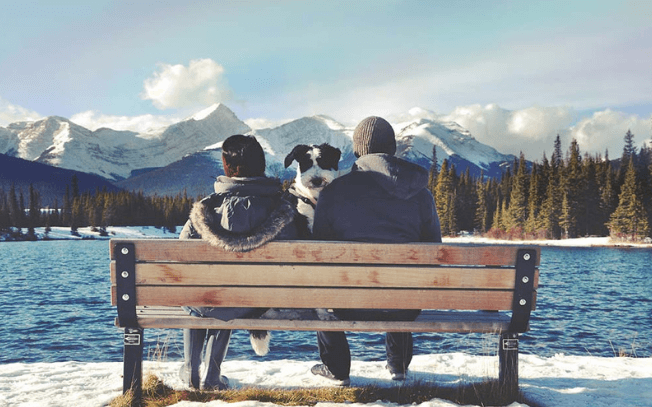 Woman, dog and man sitting on a bench with mountain in the background