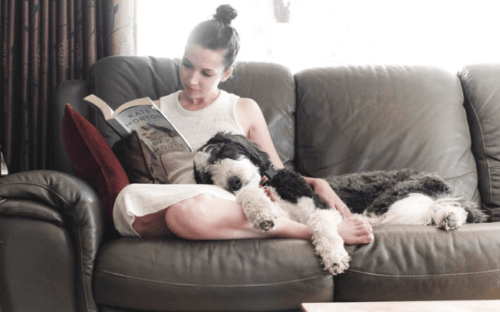Girl reading on cough while dog sleeps on her lap