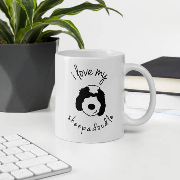 Coffee mug on a desk with a sheepadoodle cartoon face