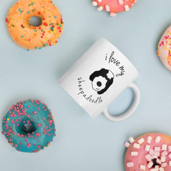 coffee mug surrouned by colorful donuts