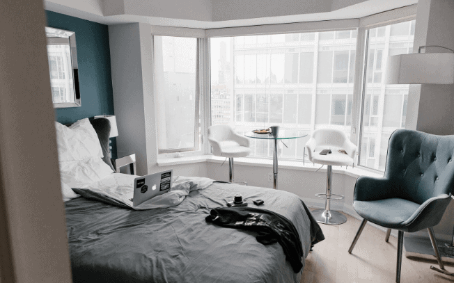 Hotel with grey bed and white chairs.