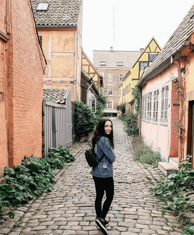 Girl walking down a narrow alley in Denmark