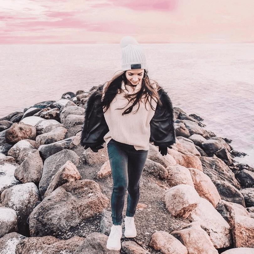 Girl walking on rocks with ocean behind