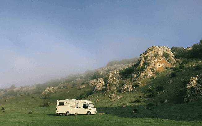An RV beside a green hill and blue sky