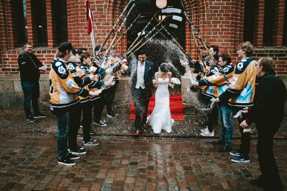 Hockey players lifting their sticks as bride and groom walk under them